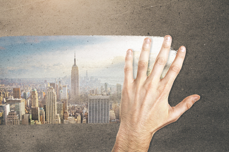 Male hand wiping concrete background and revealing city view. Imagination concept Stock Photo