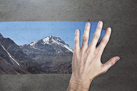 Male hand wiping concrete background and revealing mountain view. Creativity concept Stock Photo