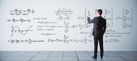 인테리어에 콘크리트 벽에 수학 수식 작성 젊은 사업가보기를 다시. 과학 개념