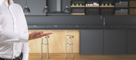 Mans hand presenting showing blurry kitchen interior with counters and equipment. Sell concept. 3D Rendering