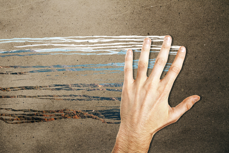 Male hand wiping concrete background and revealing mountain view. Abstract concept