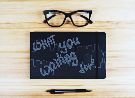 Top view of wooden desktop with glasses, pen and notepad with what you waiting for writing. Success concept