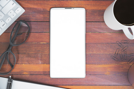 Top view of wooden office desktop with blank white mobile phone, coffee cup, keyboard, glasses and other items. Advertisement concept. Mock up, 3D Rendering