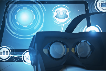 Close up of laptop and virtual reality glasses with abstract digital business hologram. Futuristic concept. 3D Rendering