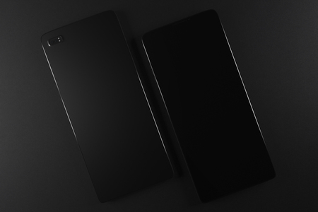 mobile communication: Two blank front and back phones with camera on black background. Model, design concept. Copy space. 3D Rendering Stock Photo