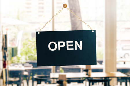 Close up of black open sign hanging on glass door of cafe. Blurry background. Information concept. 3D Rendering Banco de Imagens
