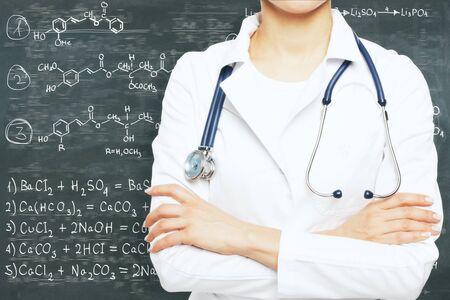Femme médecin avec les bras croisés debout sur fond tableau avec des formules chimiques . médecine et le concept de chimie Banque d'images - 86055551