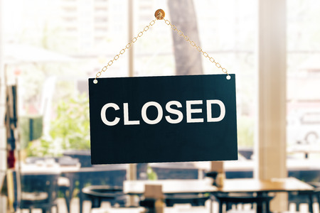 Close up of black closed sign hanging on glass door. Blurry background. Store working hours concept. 3D Rendering