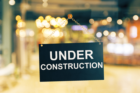 Close up of black under construction sign hanging on glass door. Blurry background. Repairs concept. 3D Rendering Stock Photo