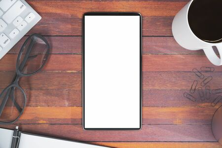 Top view of wooden office desktop with blank white cellular phone, coffee cup, keyboard, glasses and other items. Advertisement concept. Mock up, 3D Rendering Stock Photo