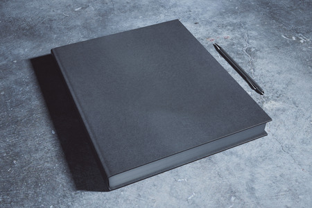 Empty black hardcover notepad and pen placed on concrete desk. Supplies, stationery items, paperwork concept. Mock up, 3D Rendering Stock Photo