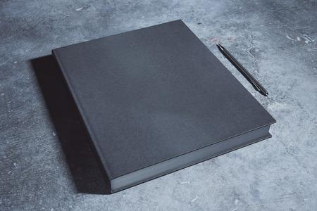 Lege zwarte hardcoverblocnote en pen die op concreet bureau wordt geplaatst. Supplies, briefpapier artikelen, papierwerk concept. Bespotten, 3D-rendering Stockfoto