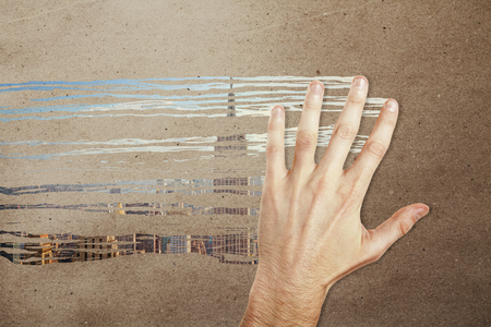 Male hand wiping concrete background and revealing city view. Inspiration concept