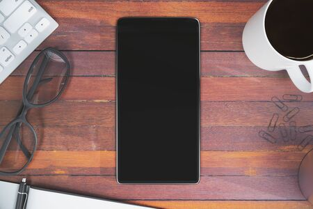 Top view of wooden office desktop with blank cellphone, coffee cup, keyboard, glasses and other items. Advertisement concept. Mock up, 3D Rendering Stock Photo