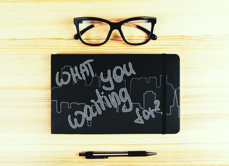 Top view of wooden desktop with glasses, pen and notepad with what you waiting for writing. Inspiration concept