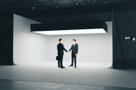 Businessmen shaking hands in modern photo studio interior with professional lighting equipment. Deal concept. 3D Rendering Stock Photo