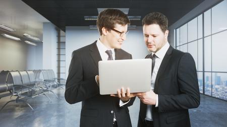 一緒に市とグランジ コンクリート オフィスでラップトップ コンピューターを使用して 2 つのハンサムな陽気なビジネスマンを表示します。会議の 写真素材