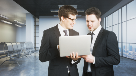 Two handsome cheerful businessmen using laptop computer together in grunge concrete office with city view. Meeting concept. 3D Rendering
