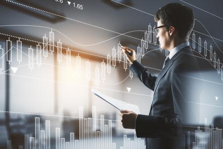 Widok z boku przystojny biznesmen z dokumentem w rękach rysowania abstrakcyjnego wykresu forex w rozmytym wnętrzu z działaniem promieni słonecznych. Koncepcja zarządzania funduszem. Podwójna ekspozycja