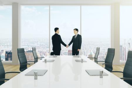 Vue de côté des jeunes hommes d & # 39 ; affaires se serrant la main dans la salle moderne de travail de l & # 39 ; équipe . concept de Banque d'images - 86797608