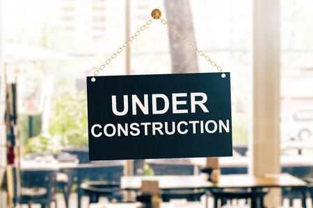 Close up of black under construction sign hanging on glass door. Blurry background. 3D Rendering