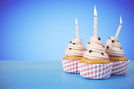 Three cupcakes with candles on light blue background with copy space. Birthday concept. 3D Rendering Stock Photo