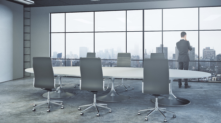 Back view of thoughtful young businessman looking out of window in modern conference room with equipment and city view. Think concept. 3D Rendering