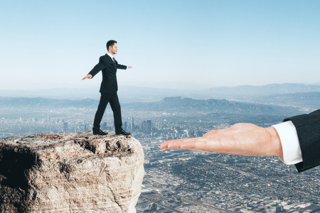 Side view of balancing businessman stepping on huge palm on city background. Risk concept