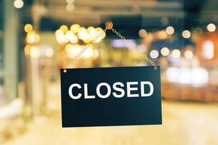 Sluit omhoog van het zwarte gesloten teken hangen op glasdeur. Wazige achtergrond. Werktijden concept. 3D-weergave