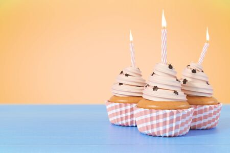 Three cupcakes with candles on light blue background with copy space. Celebration concept. 3D Rendering