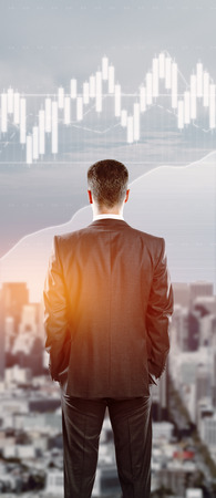 Back view of young businessman looking at city with abstract forex chart. Financial growth concept. Double exposure