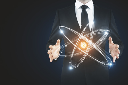 Unrecognizable businessman holding abstract glowing atom. Innovation concept Stok Fotoğraf - 87771600