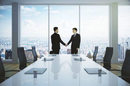 Vue de côté des jeunes hommes d & # 39 ; affaires se serrant la main dans la salle moderne de bureau. concept de partenariat . rendu 3d Banque d'images - 88325923