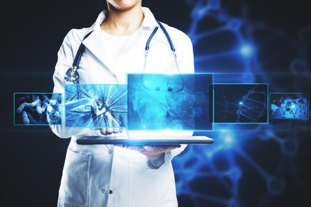 Doctora irreconocible que usa la tableta con interfaz médica digital sobre fondo oscuro con ADN. Concepto de innovación. Exposicion doble Foto de archivo