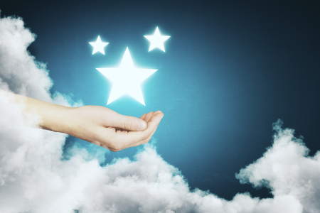Hand holding glowing star on abstract blue background with cloud. Dream concept