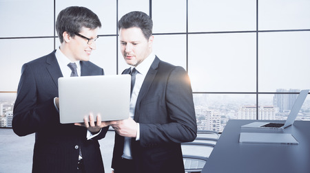 Attractive young businessmen using laptop in modern meeting room interior with city view and sunlight. Colleagues concept. 3D Rendering  Stock Photo