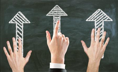 Handen die op getrokken pijlen op bordachtergrond richten. Keuze concept Stockfoto