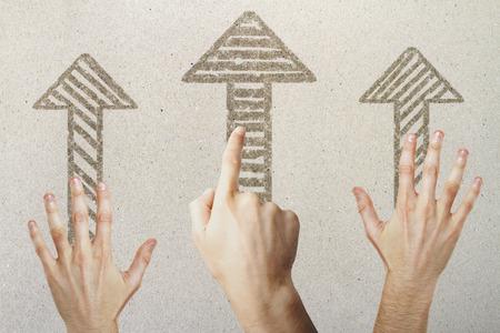 Handen die op getrokken pijlen op concrete achtergrond richten. Verschillende richting concept