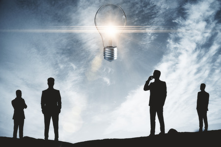 Back view of businessmen silhouettes on abstract landscape background with glowing light bulb. Innovation concept. 3D Rendering