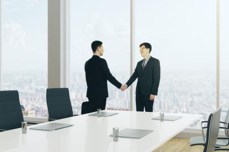 Vue de côté des hommes d & # 39 ; affaires européens se serrant la main dans la salle de travail moderne . teamwork . rendu de concept rendu 3d Banque d'images - 88676989