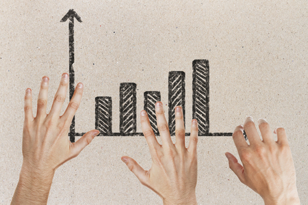 Abstract image of hands with drawn business chart on concrete background. Teamwork and finance concept