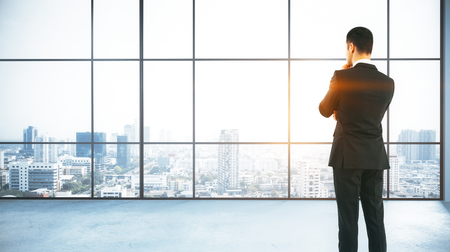 Back view of thoughtful young businessman standing in modern concrete office with panoramic city view and daylight. Research concept. 3D Rendering Imagens - 88477910