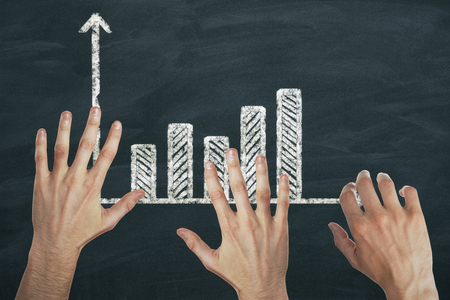 Abstract image of hands with drawn business chart on chalkboard background. Teamwork and money concept
