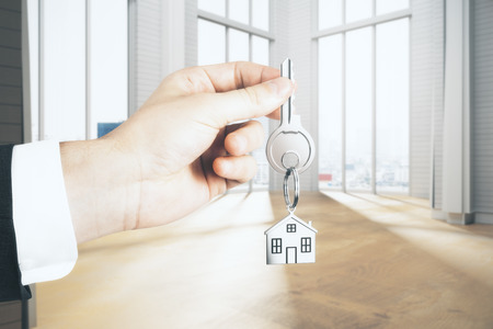 Businessman hand holding key with house chain in interior with city view and sunlight. Rent concept. 3D Rendering  Banco de Imagens