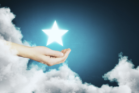 Hand holding glowing star on abstract blue background with cloud. Achievement concept