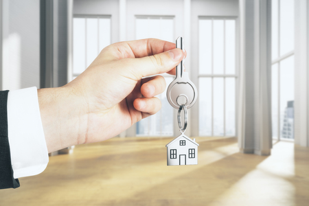 Businessman hand holding key with house chain in interior with city view and sunlight. Mortgage concept. 3D Rendering