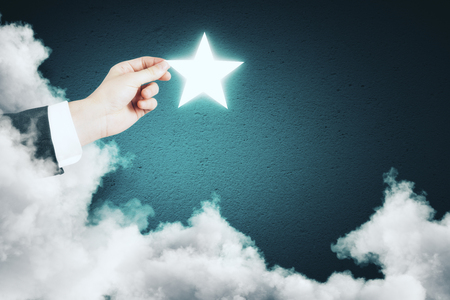 Hand holding glowing star on abstract blue background with cloud. Imagination concept