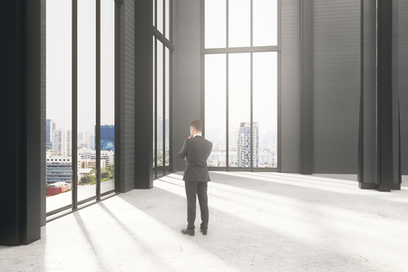 Pondering young businessman in empty interior with city view and sunlight. Research concept. 3D Rendering  Stok Fotoğraf
