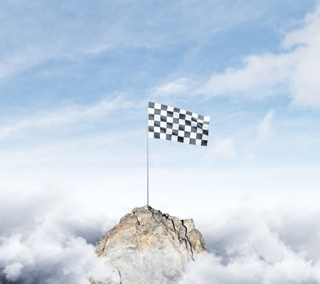 Checkered flag on mountain top. Cloudy sky background. Achievement concept