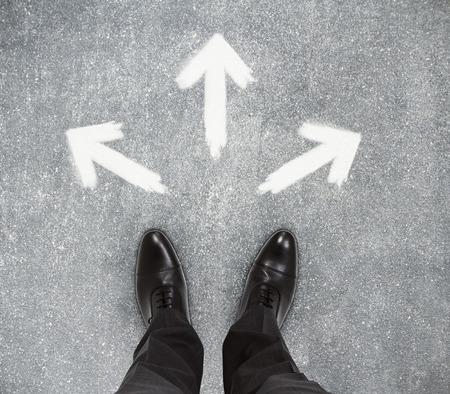 コンクリートの床に描かれた矢印のビジネスマンの足の平面図です。コンセプトに従ってください。